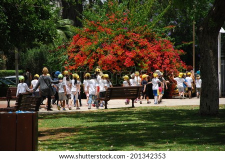 Tel Aviv, May 25, 2014. Schoolchildren group walking in a park together with their educators.