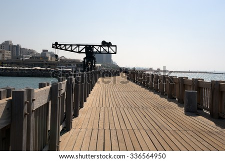 TEL-AVIV - OCTOBER 17, 2015: A restored old crane, with restaurants and commercial area in the background, in Tel-Aviv Port, Israel. The port compound was restored as a dining and commercial area