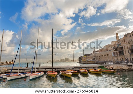 Tel Aviv - The little harbor and yachts under old Jaffa and Tel Aviv in the backgound in the morning light and man at fishing. - stock photo