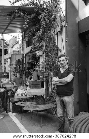 TEL AVIV-YAFO, ISRAEL - FEBRUARY 18, 2014: Two unidentified vendors of secondhand stores waiting for the clients. Jaffa flea market (Shuk Hapishpeshim) is popular attractions for tourists and locals.