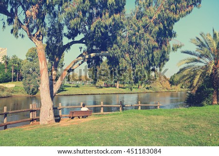 Tel Aviv Yarkon public park. Riverside. Green area for recreation and sports with  playgrounds. Man relaxing on a bench in the shade of an old eucalyptus tree on the lawn. Toned vintage colors photo
