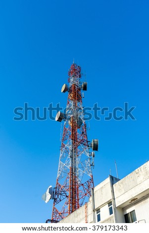 Telecommunication antenna on the building for radio, television and telephone with blue sky background.