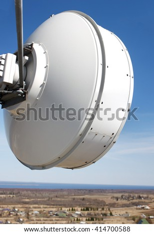 telecommunication antenna round. transceiver antenna cellular closeup. against the backdrop of the forest, houses and roads - stock photo