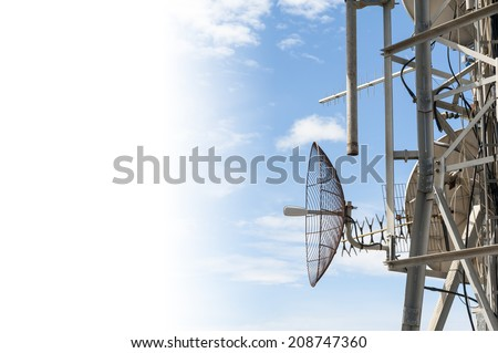 Telecommunication antenna tower against the blue sky with white copyspace - stock photo