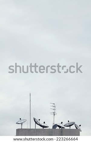 Telecommunication concept. old fashioned satellite antenna against cloudy sky. - stock photo