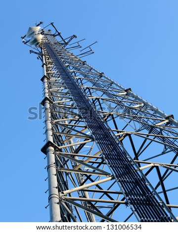 Telecommunication mast with antennas over a blue sky - stock photo