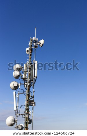 Telecommunication mast with microwave link antennas over a blue sky - space for Your text - stock photo