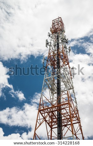 Telecommunication tower against blue sky blue and white clouds