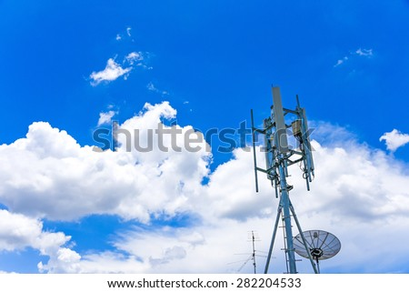 telecommunication tower and satellite dish under cloudy blue sky