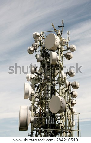 Telecommunication tower covered with various antennas against blue sky with clouds - stock photo