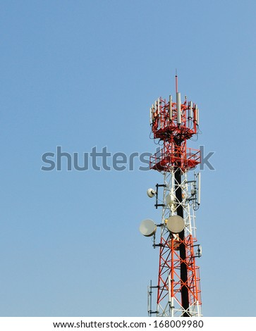 Telecommunication tower - dish antenna tall red and white pole blue sky