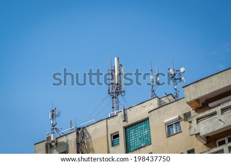 Telecommunication tower on blue sky mounted on a flat - stock photo