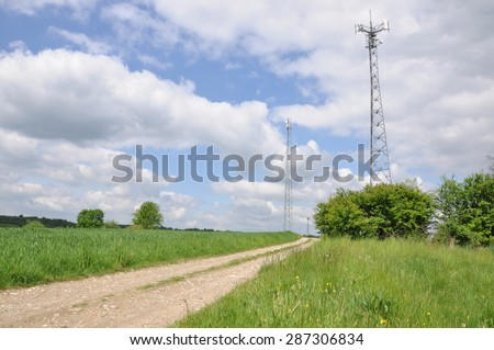 Telecommunication tower on the field against the sky  - stock photo