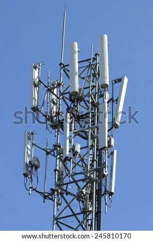 Telecommunication tower with antennas over a blue sky. - stock photo