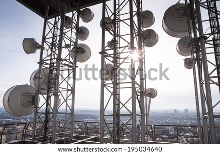 Telecommunication tower with many satellite dishes in the city - stock photo