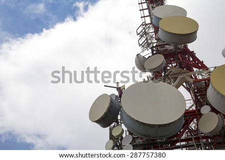 Telecommunication tower, with multiple satellite dishes - stock photo