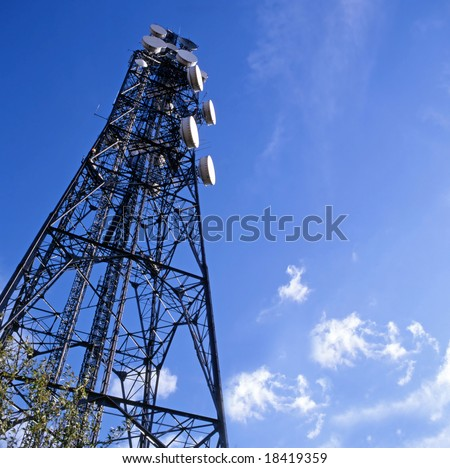 Telecommunications mast set against blue sky and small clouds - stock photo