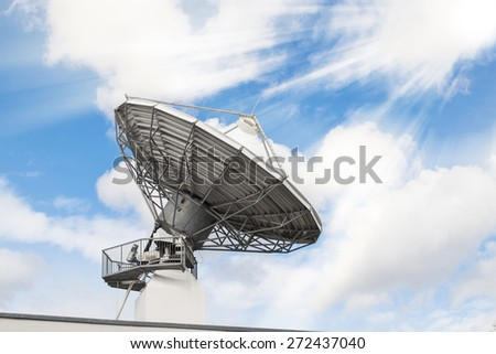 Telecommunications radar parabolic radio antenna as part of global communication technology stations system against sunny sky with sun rays sunbeams. Toned and filtered stock photo. - stock photo