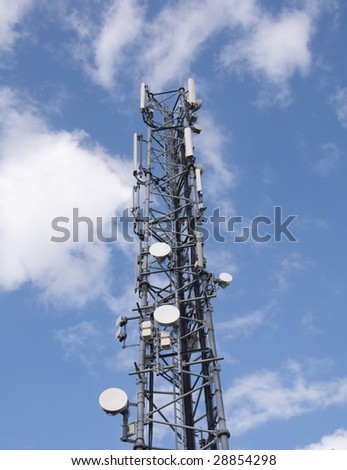 telecommunications tower micro waves dished. phone cell 3g and 4g antenna aerials tower high into blue sky and clouds. large industrial communications radio tower transmission.