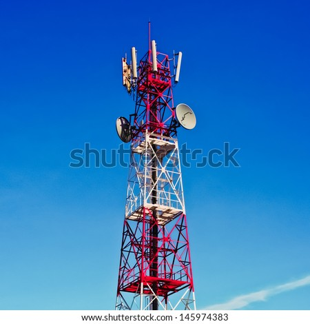 Telecommunications tower, painted white and red in a day of clear blue sky.