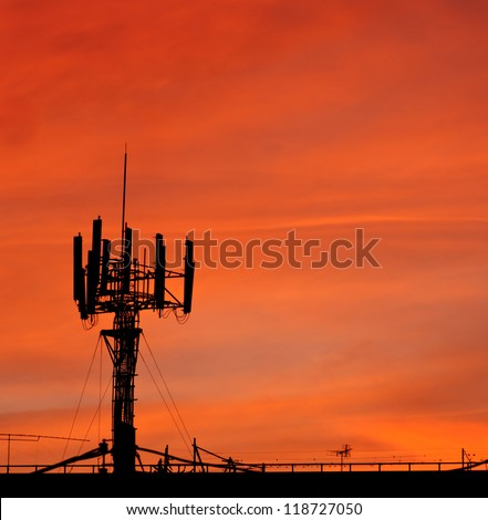 telecommunications tower with sunset sky, silhouette - stock photo