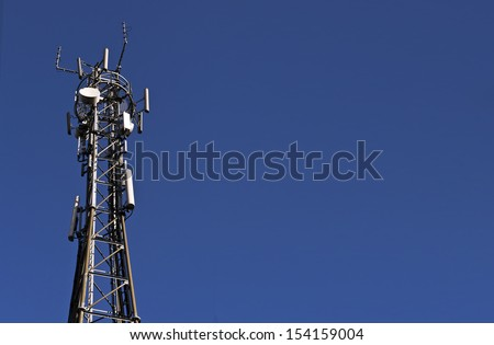 Telecoms/cellphone mast; isolated against deep blue sky; excellent and extensive copy-space  - stock photo