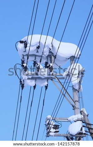Telegraph pole with snow.