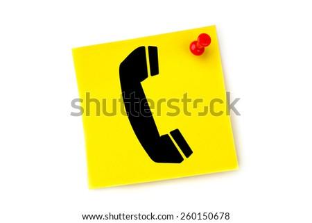 Telephone against yellow pinned adhesive note - stock photo