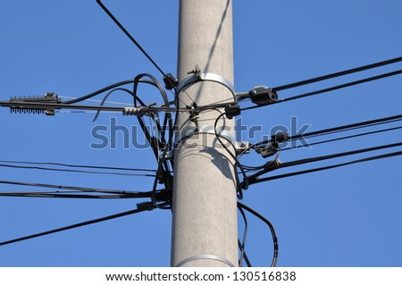Telephone cable lines on a pole against a blue sky - stock photo