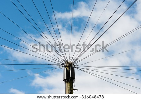 Telephone communication wires connected to a central pole against a blue sky and clouds. - stock photo