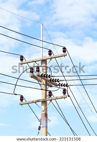 telephone utility poles, cables, streetlights, and clear blue sky background