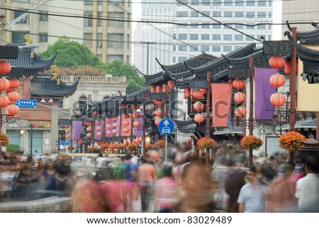 Telephoto image of many people on Chinese street. Shopping street in Shanghai. - stock photo