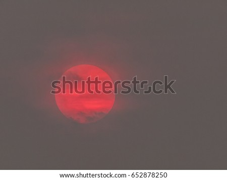 Telephoto shot of a large, red setting sun in Thailand