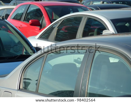 Telephoto view of cars parked in parking lot. Image can be reversed for non British uses. Also useful for environmental issues. - stock photo