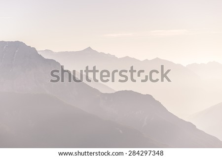 Telephoto view of distant marsala toned mountain range at sunrise with clear sky and soft light. - stock photo