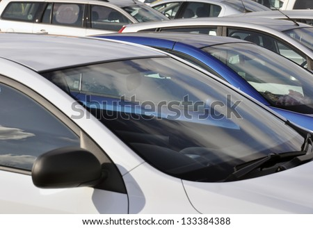 Telephoto view of parked vehicles in car park - stock photo