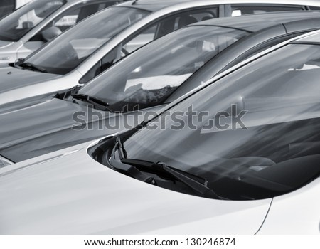 Telephoto view of vehicles parked in parking lot - stock photo