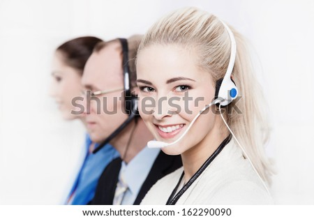 Telesales or helpdesk team - helpful woman with headset smling at camera - stock photo