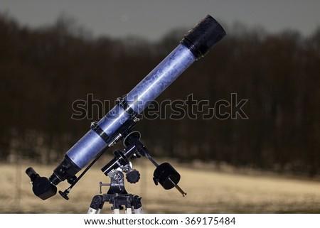 Telescope in night sky Winter edition frozen telescope Refractor Telescope - stock photo