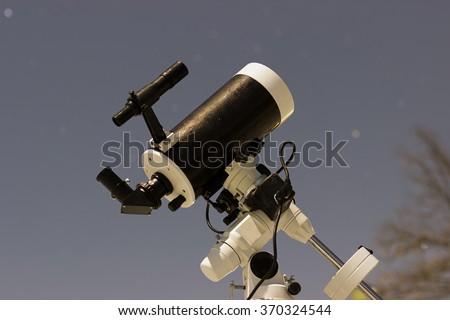 Telescope in night sky Winter edition Maksutov Cassegrain Telescope - stock photo