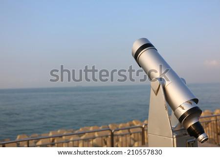 Telescope on the beach in Qingdao of china - stock photo