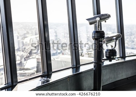 Telescopes overlooking a city on an observation deck at a high tower - stock photo