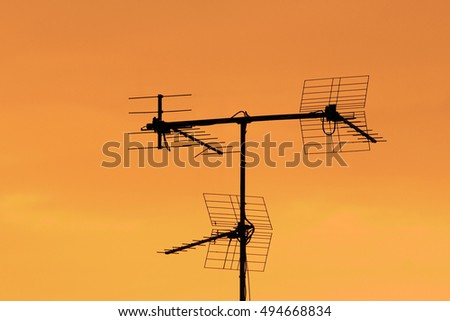 Television antenna silhouette over orange background