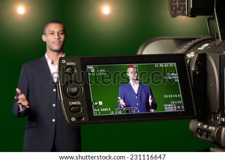 Television presenter recording in a green screen studio, seen through the LCD display of a digital TV camera. Selective focus on the viewfinder.