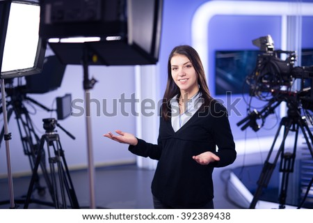 Television presenter recording in television news studio.Female journalist anchor presenting business report.News camera,light equipment behind the scenes.Talking at camera to the TV audience. - stock photo