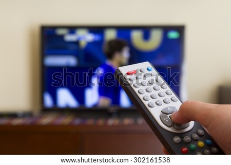 Television remote control in human hands, watching a football match
