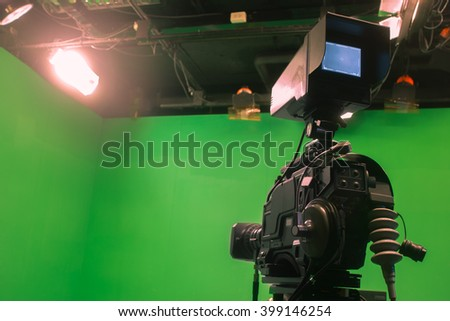 Television studio with camera and lights - camera on green screen - stock photo