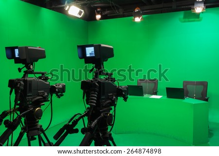 Television studio with camera and lights - camera on tripod: Shallow depth of field - stock photo