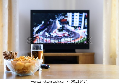Television, TV watching (formula one race) with snacks and alcohol on table - stock photo - stock photo