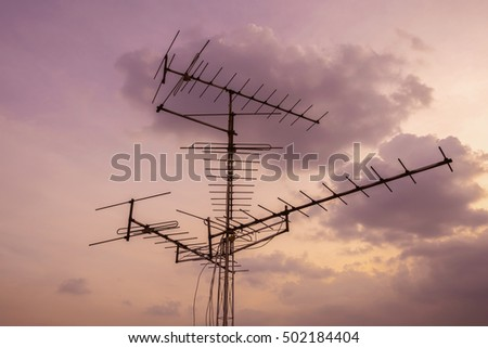 televisions antennas on top building with sunset cloudy sky background